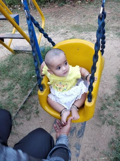 Midsection Of Man By Girl Sitting On Swing