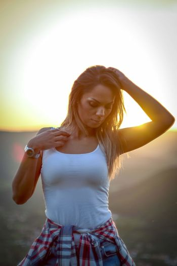 Beautiful woman standing against sky during sunset