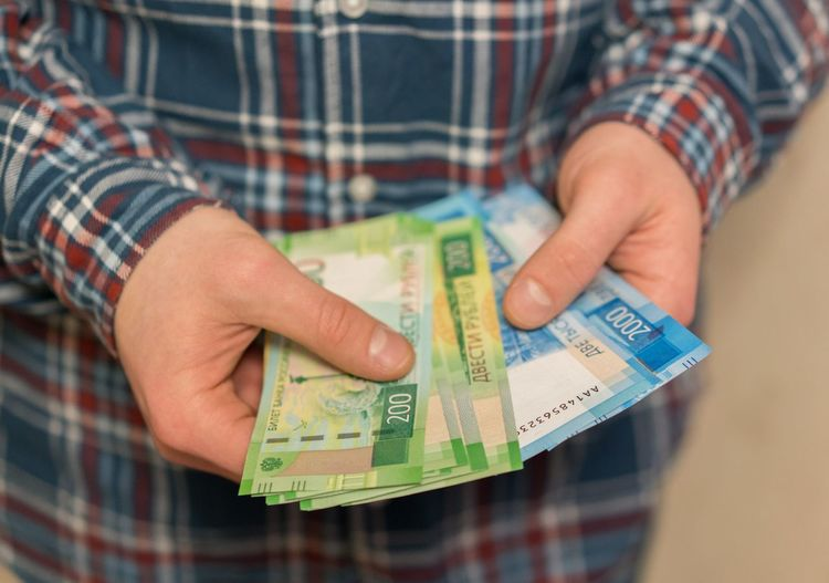 Midsection of man holding paper currencies
