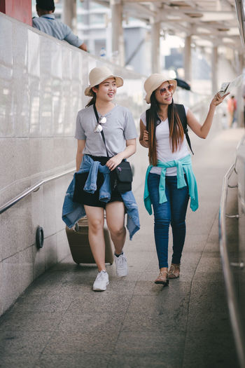 Full Length Two People Young Women Young Adult Hat Real People Lifestyles Casual Clothing Front View Architecture People Togetherness Smiling Fashion Women Clothing Portrait Leisure Activity Glasses