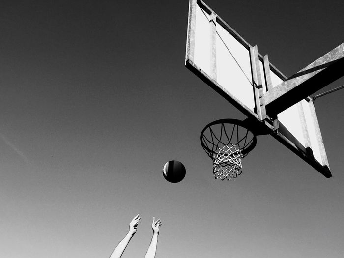 Cropped hands throwing ball in basketball hoop against sky