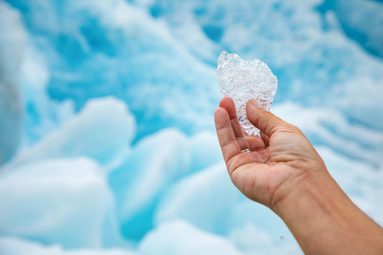 Cropped image of person hand holding ice against icebergs