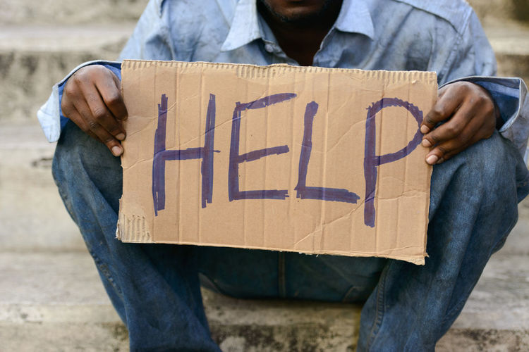 Midsection of beggar holding cardboard with text