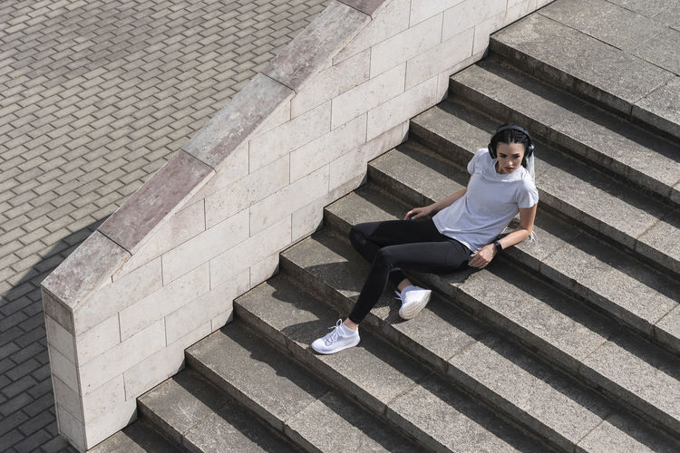 High angle view of man sitting on staircase