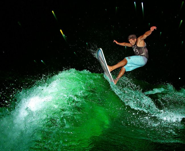 Low angle view of man wakeboarding in illuminated sea at night