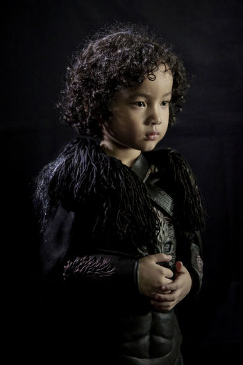Little Jon Snow Boy Curly Medieval Costume Game Of Light Game Of Thrones Jon Snow Halloween Model Cute Toddler  Fierce Stark Black Background Child Portrait Childhood Girls Studio Shot Beauty Pleading Beautiful People Females Head And Shoulders Babyhood Dressing Up Baby Clothing Disguise Superhero