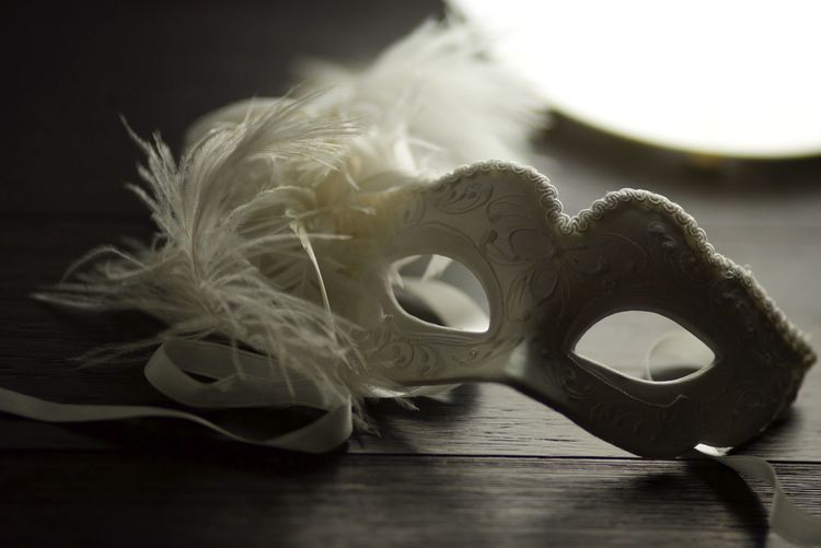 Close-up of eye mask with feather on table