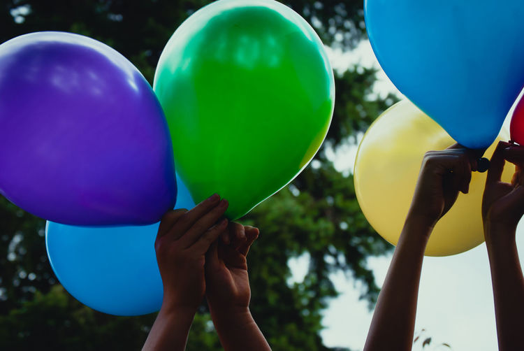 Cropped image of people holding multi colored balloons