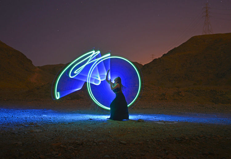 Full length of man standing by illuminated light painting at night
