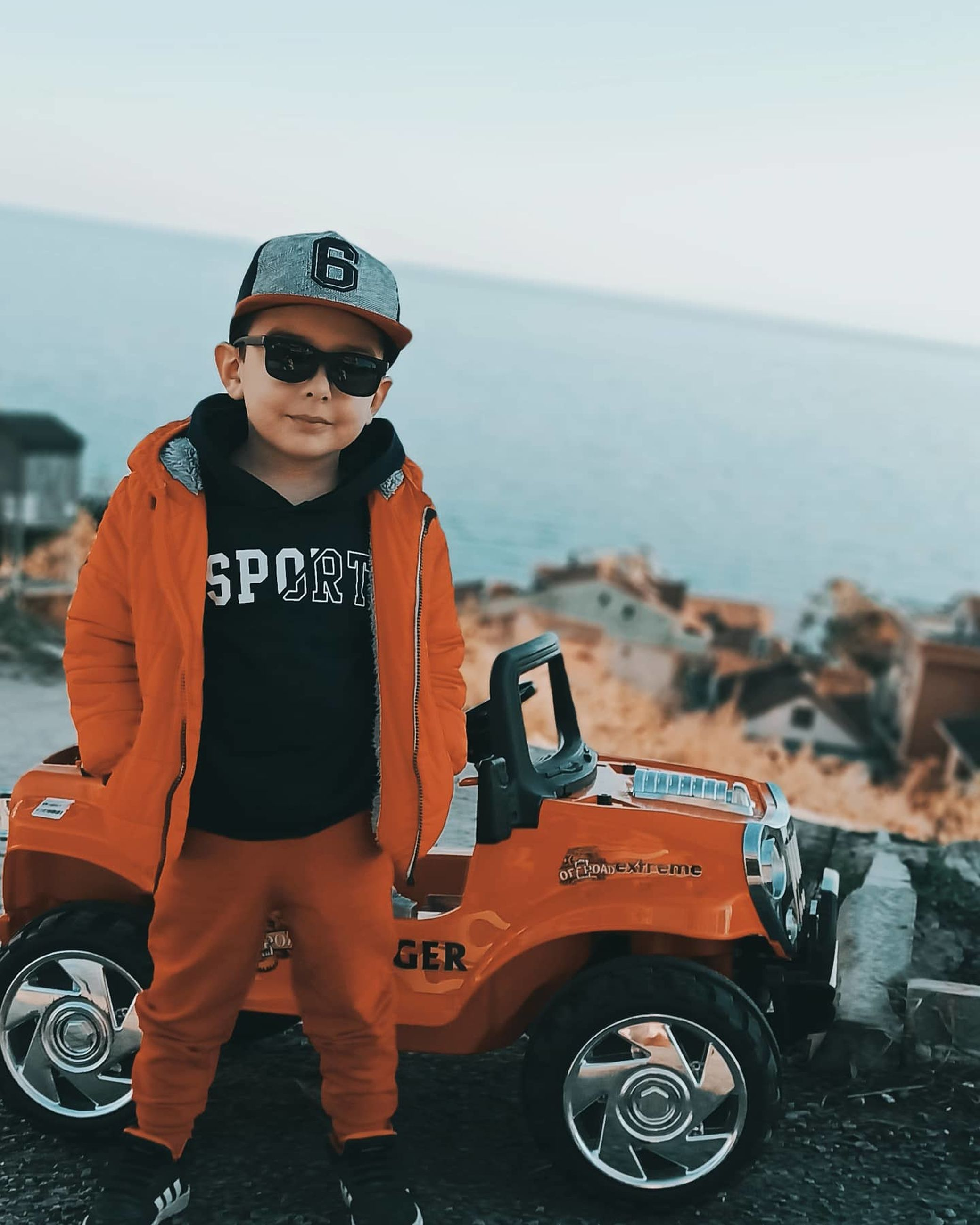 one person, sunglasses, transportation, full length, standing, vehicle, fashion, portrait, glasses, sea, mode of transportation, looking at camera, day, car, adult, sky, men, nature, protection, childhood, outdoors, security, water, child, front view, sports, clothing, leisure activity, land, casual clothing, beach, occupation