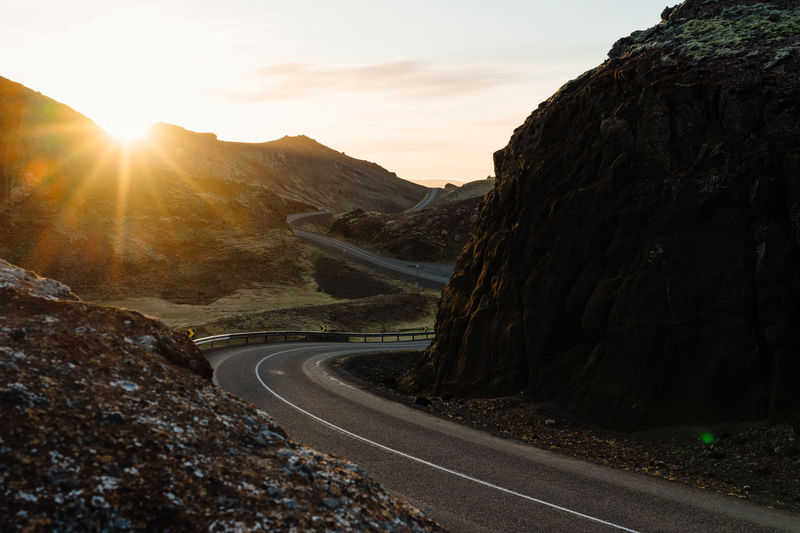 Road amidst mountains against sky during sunset
