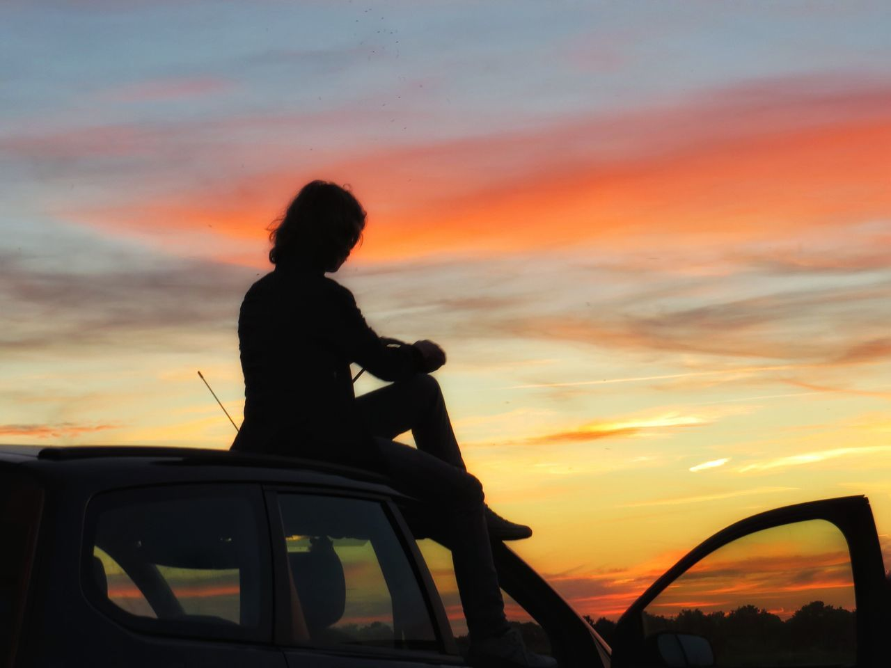Silhouette of man against cloudy sky at sunset
