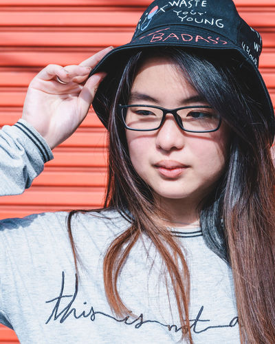 Red Red Background Real People One Person Front View Glasses Portrait Hair Young Adult Casual Clothing Lifestyles Eyeglasses  Hairstyle Leisure Activity Young Women Headshot Long Hair Close-up Looking At Camera Text Dyed Hair Teenager