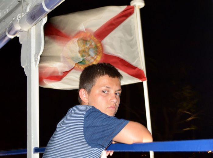 Portrait of boy against flag waving at night