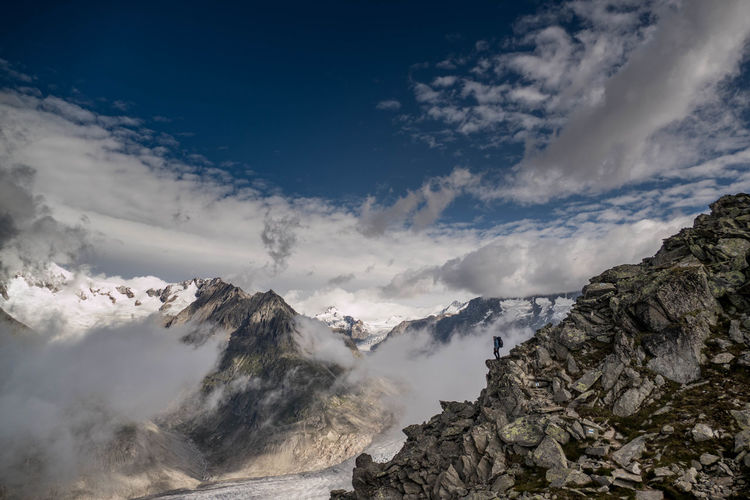 hiker in the swiss alps at a great height near a glacier Hiking Ice View Altitude Beauty In Nature Cloud - Sky Cold Temperature Day Glacier Hiker Landscape Mountain Mountain Range Nature Outdoors Person Rocks Scenics Sky Snow Swiss Switzerland Tourism Tranquil Scene Tranquility