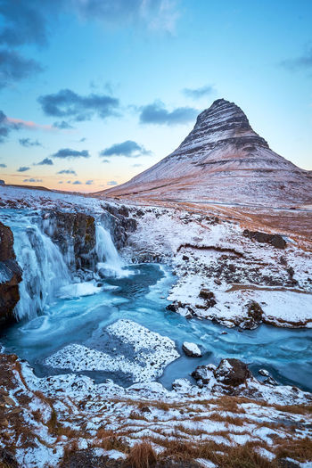 Scenics - Nature Beauty In Nature Sky Cold Temperature Winter Snow Mountain Cloud - Sky Tranquil Scene Environment Non-urban Scene Water Tranquility Nature No People Landscape Idyllic Snowcapped Mountain Flowing Water Kirkjufell Iconic Day Outdoors Mountain Peak