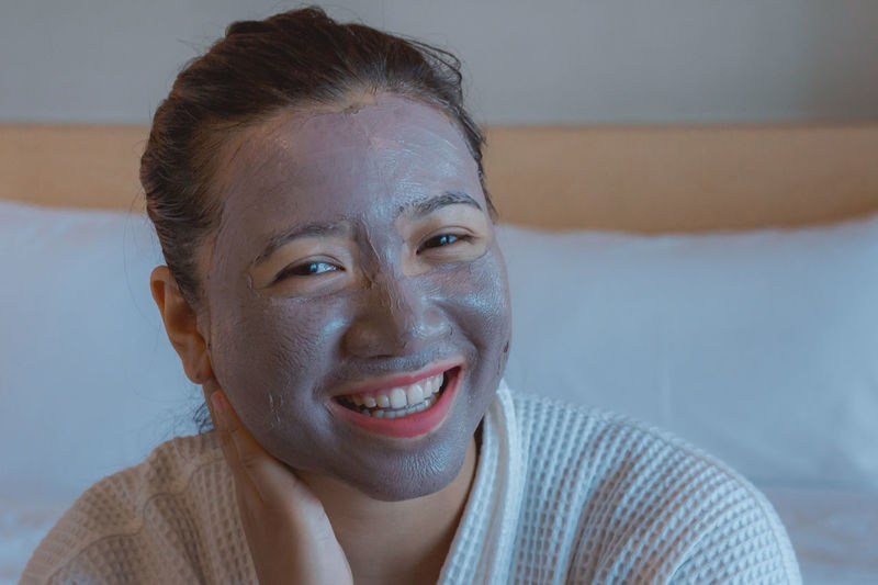 Portrait of woman with facial mask on bed at home
