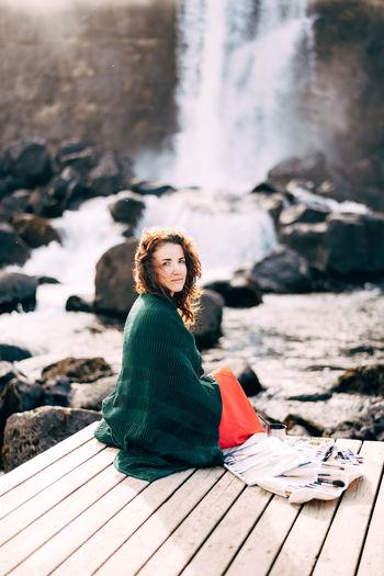 Portrait of woman sitting on rock by water