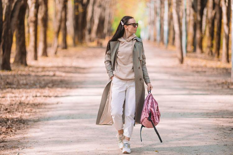 Woman with umbrella walking on street