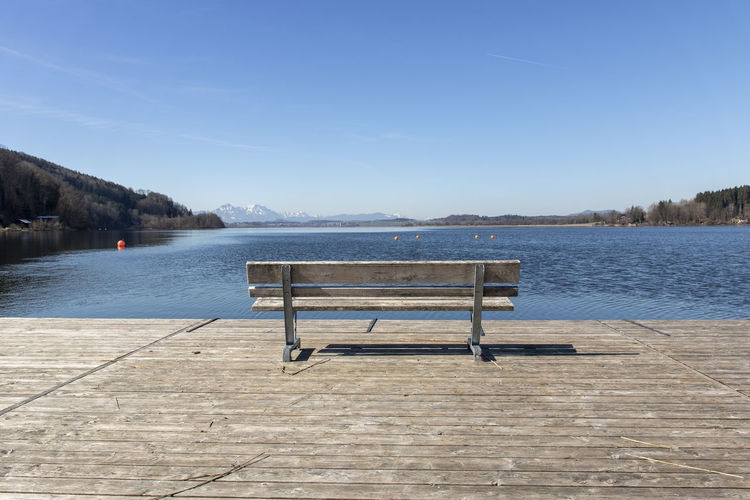 Empty bench by lake against blue sky