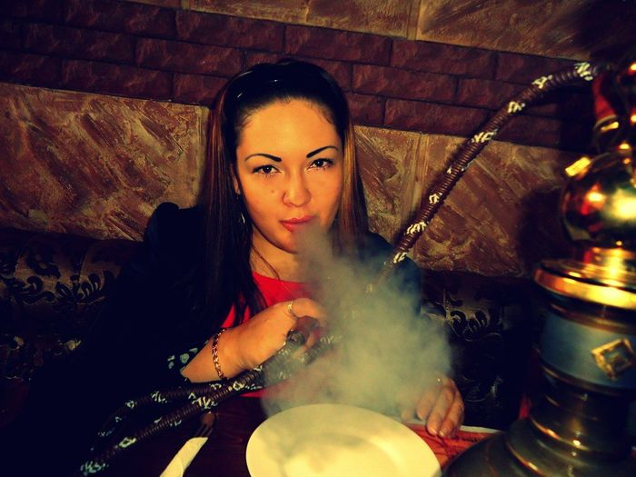 Portrait Of Young Woman Smoking Hookah