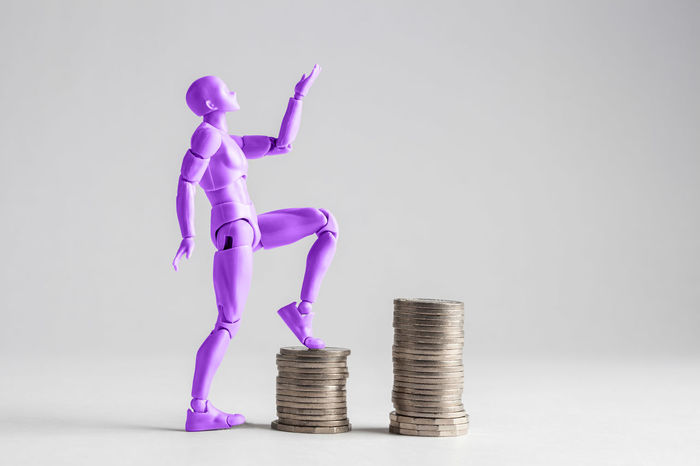 Empowered women stepping up the income ladder concept. Purple female figurine clilmbing up on piles of coins. Isolated on white with copy space. Business Coin Concept Conceptual Copy Space Currency Figurine  Finance Gender Equality Savings Stack Studio Shot Wage Gap Walking Up The Stairs Wealth White Background Woman