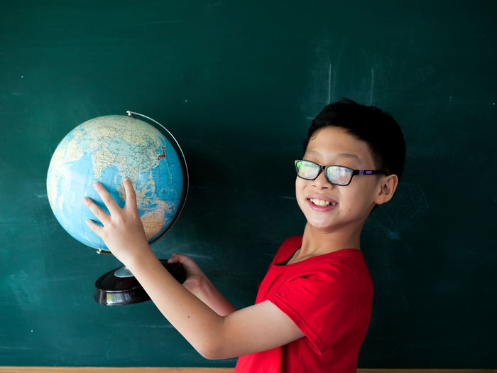 Portrait of boy wearing eyeglasses while holding globe against black board