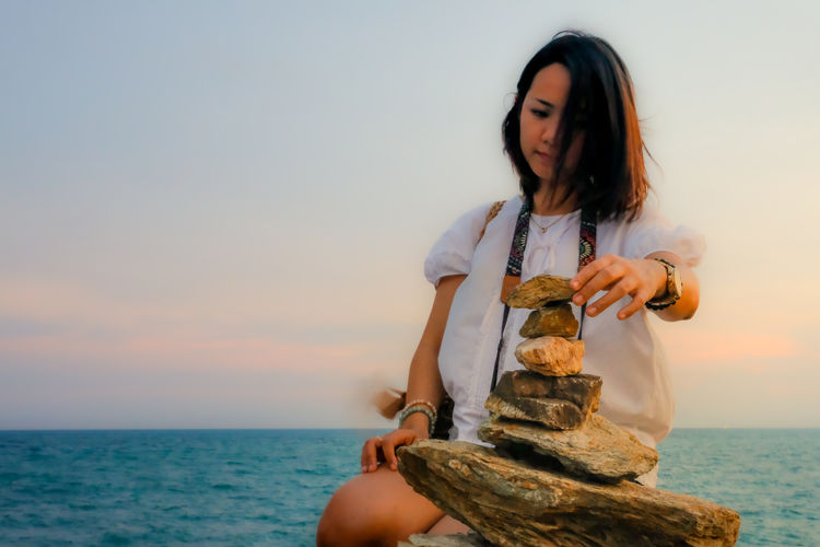 Low angle view of woman stacking rocks against sea during sunset