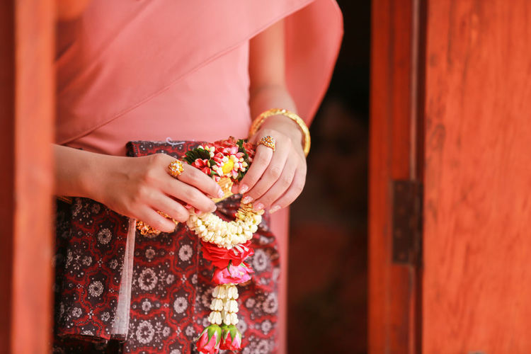 Midsection of woman holding flower garland