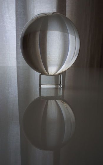 Close-up of lamp on table against wall