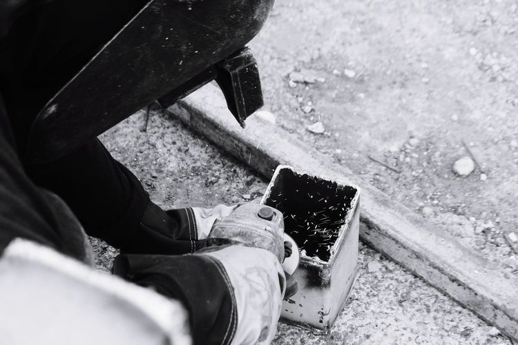 High angle view of man cutting metal at construction site