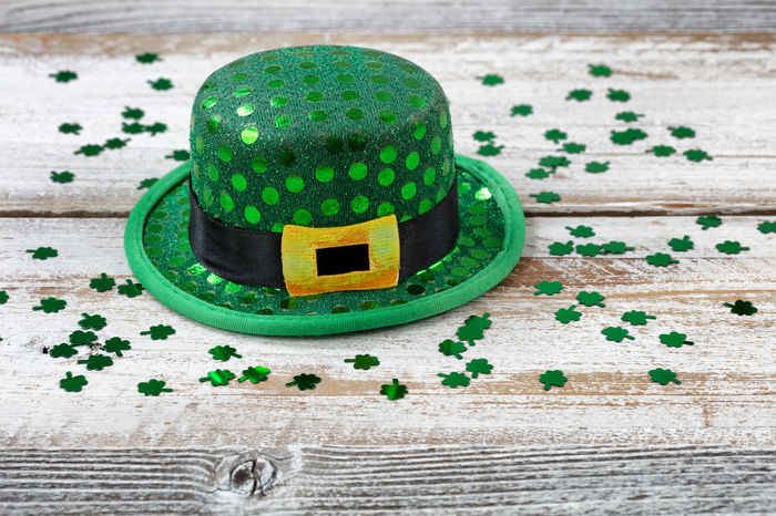 St Patrick day good luck hat with shiny clovers on rustic white wooden boards in close up view Clover Green Color Hat Holiday Luck St Patrick's Day Wood Gold Colored Irish St Patrick