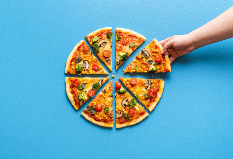 Directly above shot of hand holding pizza against blue background