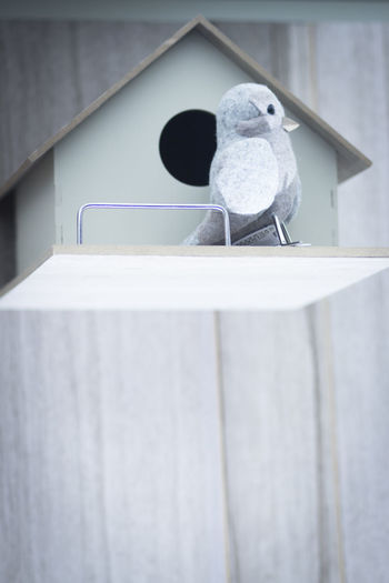 Small stuffed toy on railing against wall