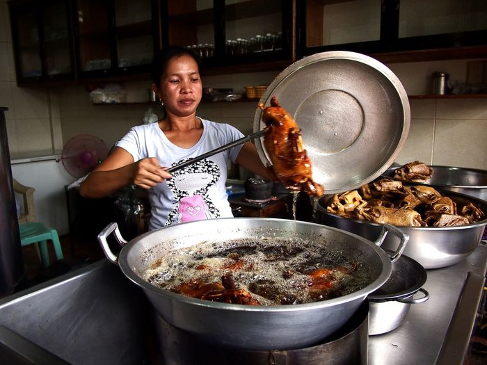 Asian woman deep frying ducks in her restaurant's kitchen Asian  Asianfood Filipino Filipino Food Duck Fried Duck Deep Fried  Cooking Oil Cooking Cook  Poultry Fried Itik Angono, Rizal, Philippines Meal Lunch Dinner Breakfast Stove Chef Commercial Kitchen Preparation  Food And Drink Establishment Food And Drink Frying Pan Cooking Pan Wok Preparing Food Gas Stove Burner Pan Boiling