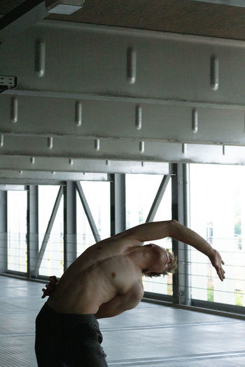 Side view of man leaning against ceiling