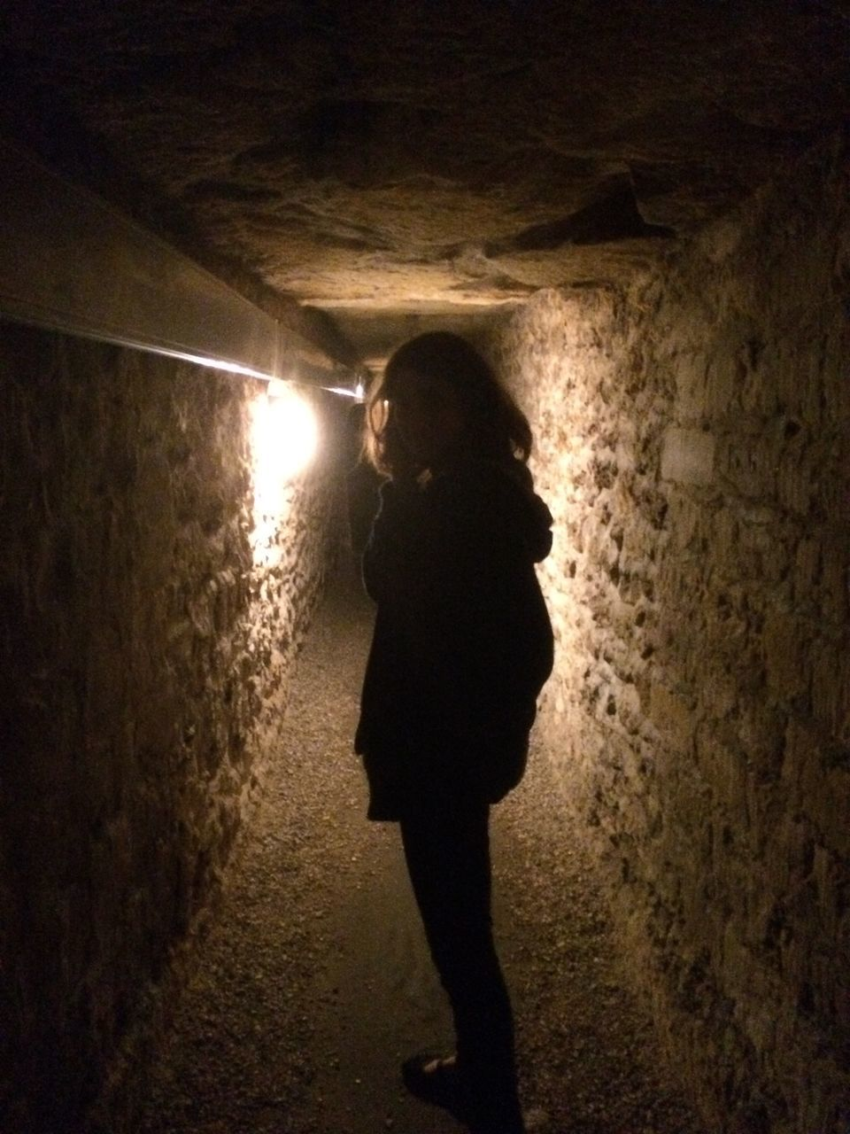 Woman Standing In Illuminated Tunnel