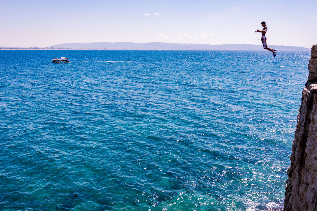 sea, real people, leisure activity, water, one person, lifestyles, full length, outdoors, adventure, weekend activities, mid-air, nature, scenics, vacations, day, men, beauty in nature, horizon over water, sport, clear sky, sky, extreme sports, people