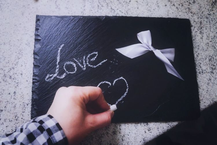 Cropped hand of person drawing heart shape on slate