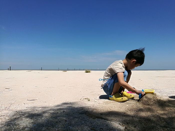 Boy playing on sand at beach against sky