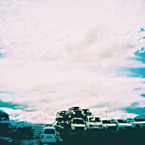 Cars on road against cloudy sky