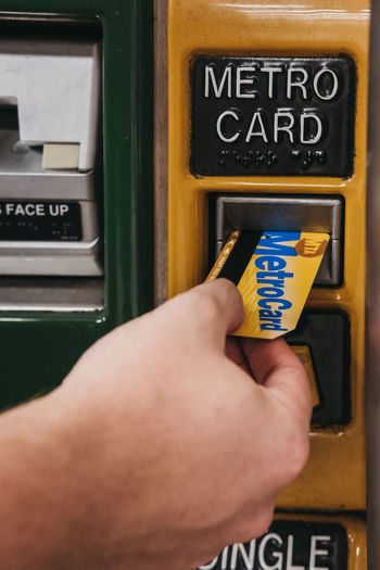 Male hand puts Metro Card into a top up machine at a subway station in New York. A MetroCard is used as a ticket and can operate in two modes: Regular and Unlimited Ride. Tourism Travel United States USA New York City New York Metrocard Human Hand Real People Close-up Holding Ticket Machine Travel Destinations Commute Card Tickets Top Up Subway Metro NYC Everyday Lives Commuter Mta Machine Subway Station