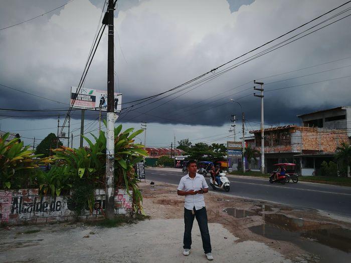 Man standing on street against sky in city