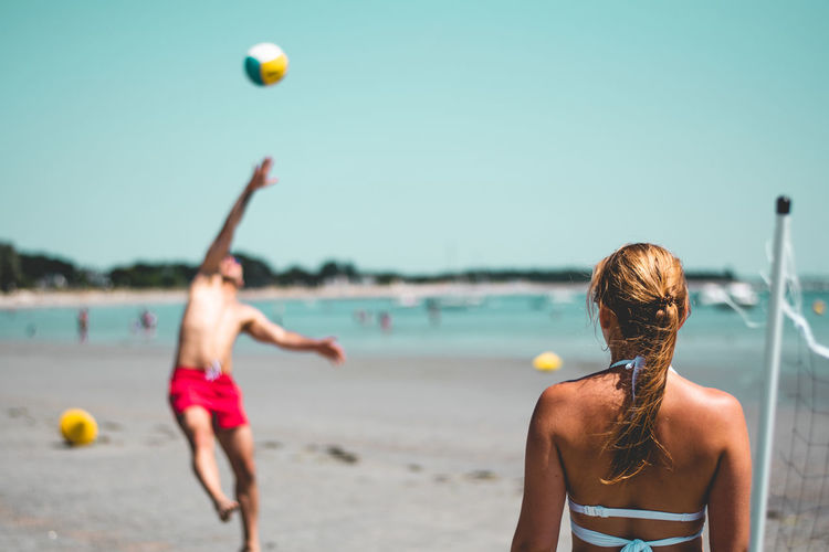 Couple Playing Volley Ball While Standing At Beach Against Clear Blue Sky During Sunny Day