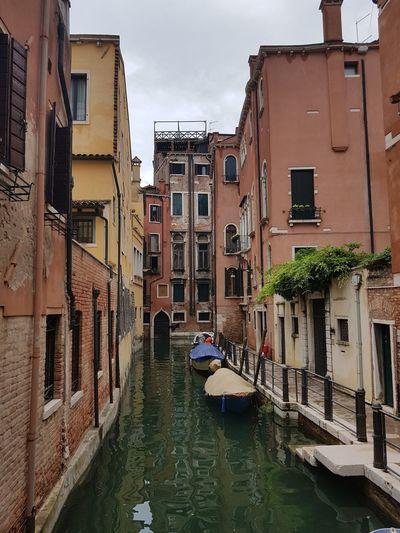 Venice canal amidst buildings in city against sky