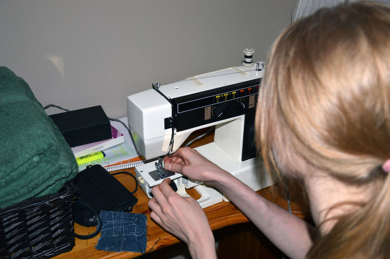 High angle view of woman working on sewing machine at home