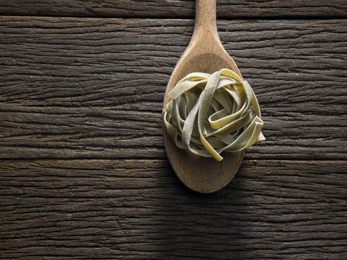 wooden spoon with tagliatelle pasta Dried Food Food And Drink Spaghetti Tagliatelle Carbohydrate - Food Type Close-up Directly Above Eating Utensil Food Healthy Eating High Angle View Indoors  Ingredient Italian Food Kitchen Utensil No People Pasta Raw Food Spoon Still Life Textured  Wood - Material Wood Grain Wooden Spoon Yellow