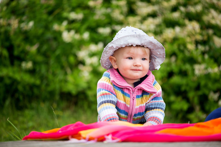 Close-up of cute baby girl sitting on blanket at park