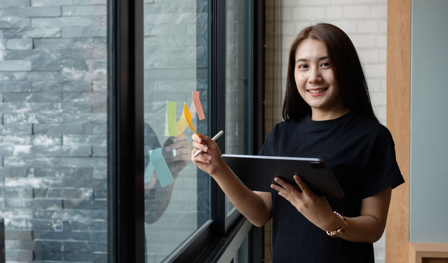 Portrait of a smiling young woman standing by window