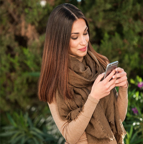 Young woman looking away while using mobile phone